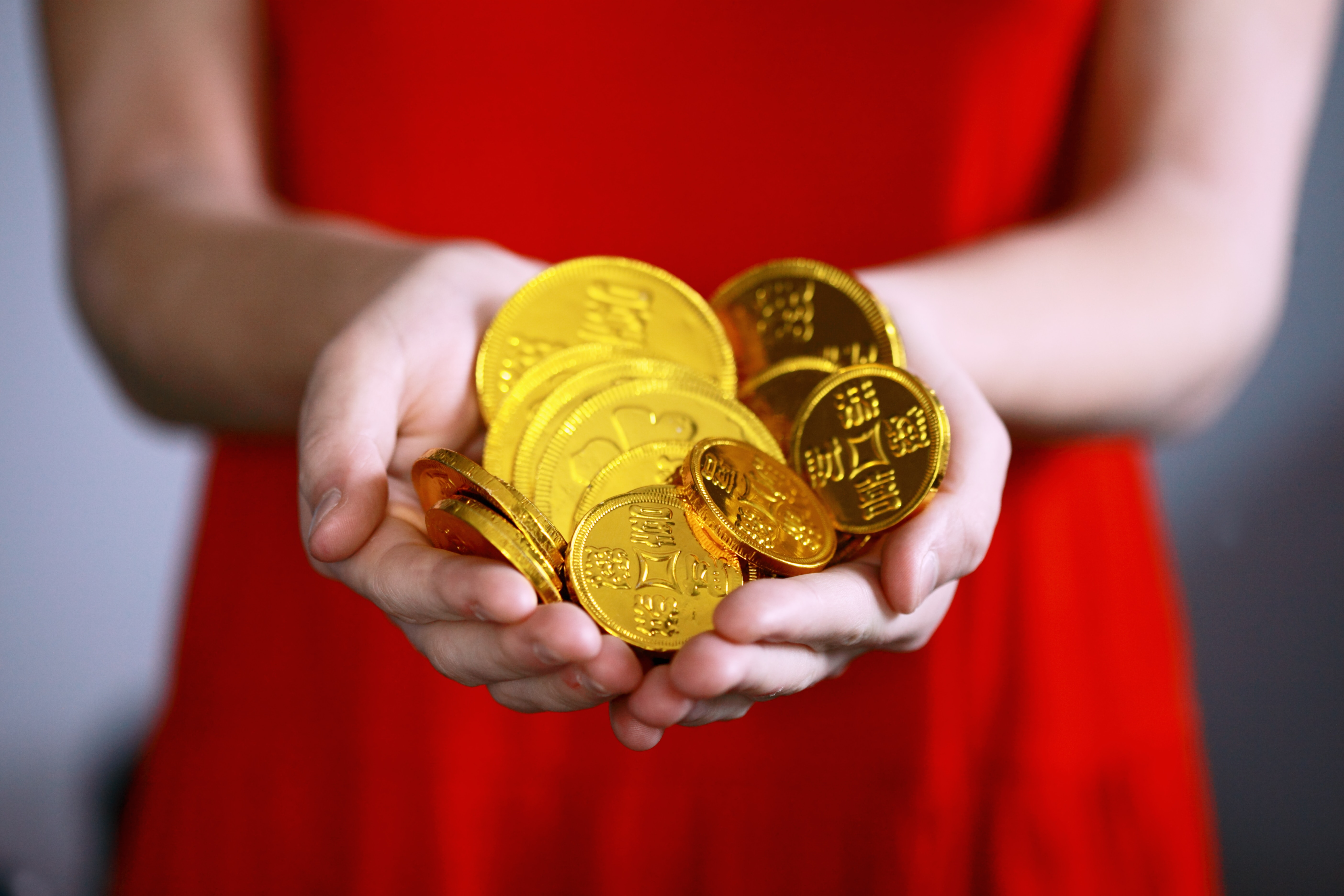 Image of woman holding gold coins
